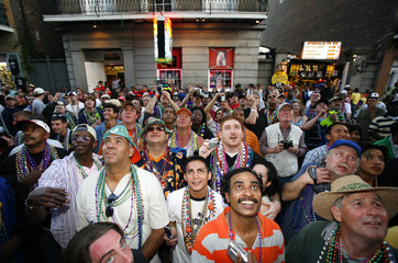 Revelers ogle at woman exposing herself on Bourbon St. during Mardi Gras festivities in New Orleans