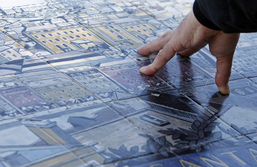 A tourist looks at a tile-painting of city of Lisbon