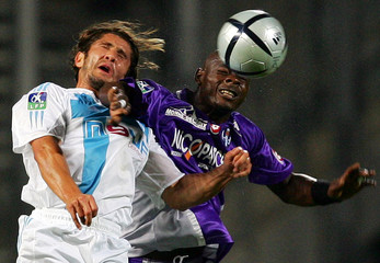 Toulouse's Emana jumps to head ball against Marseille's Lizarazu during their French Ligue 1 soccer ...