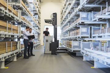 Two men with documents and worker with forklift in factory warehouse