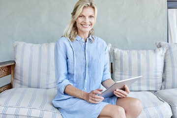 Portrait of smiling blond woman sitting on couch with tablet