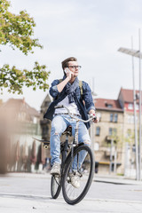 Young man with bicycle in the city talking on cell phone