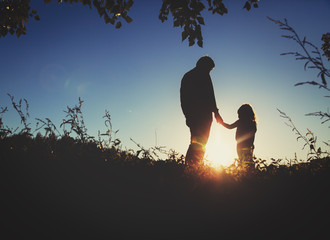 father with little daughter walk at sunset
