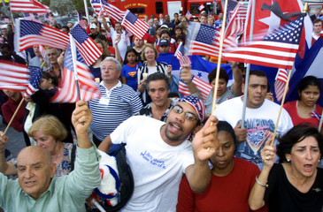 MIAMI RESIDENTS WAVE FLAGS AND SING THE NATIONAL ANTHEM AFTER MEMORIALSERVICE.