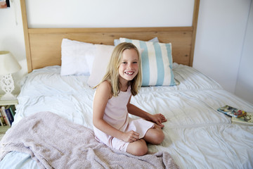Portrait of smiling little girl sitting on bed at home