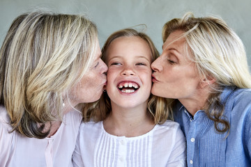 Portrait of happy little girl kissed by mother and grandmother