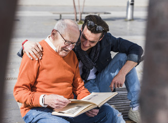 Senior man and adult grandson on a bench looking at photo album