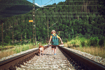 Little boy with big backpack and his beagle dog run on railway