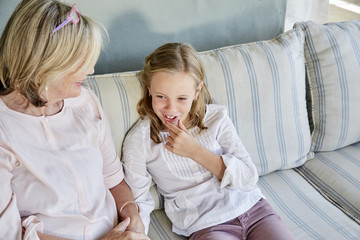 Smiling little girl sitting beside her grandmother on the couch