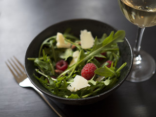 Fresh rocket salad with raspberries, roasted almonds and cheese in black ceramic bowl, and a glass of white wine on black wooden table