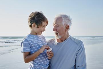 Großvater mit Enkelsohn auf dem Arm am Strand