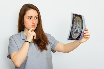 Young female doctor looking at the x-ray picture on white background