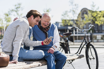 Senior man and adult grandson on a bench looking at cell phone