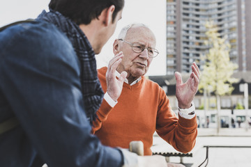 Senior man talking to adult grandson outdoors