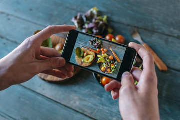 Close-up of man's hands taking picture of avocado salad with smartphone