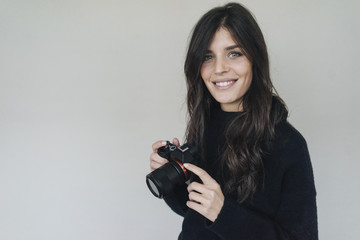 Smiling dark-haired young woman holding a camera
