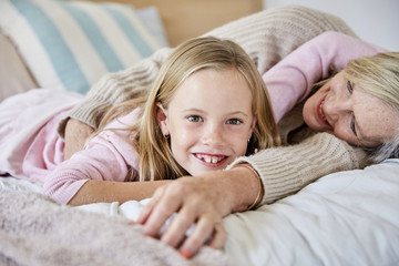 Portrait of happy little girl lying on the bed with her grandmother