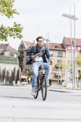 Young man with bicycle in the city holding cell phone