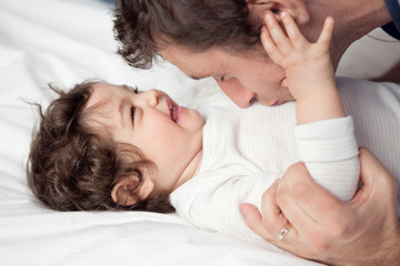 Dad kissing her laughing baby girl on the stomach
