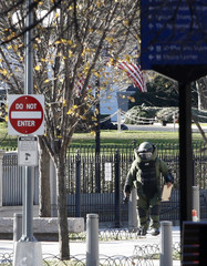 A bomb defusal expert walks towards a suspicious package left outside the front of the U.S. Treasury building near the White House (background) in Washington