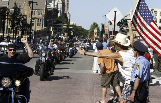 Wil Huntington of Milwaukee waves an American flag as Harley-Davidson motorcycle riders parade through the streets