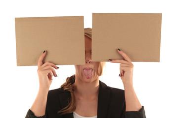 Frau versteckt Augen hinter Schildern und streckt frech die Zunge raus