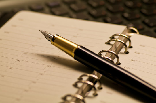 デスクの上に置かれた万年筆と手帳