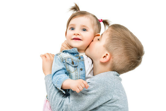 Brother kissing his little cute sister, isolated on white background