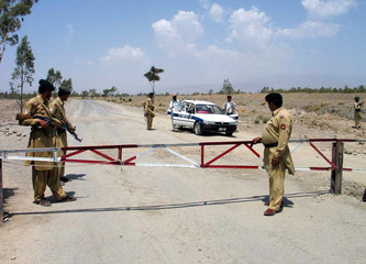 PAKISTANI PARAMILITARY SOLDIERS STAND GUARD AT A CHECKPOINT ON THE OUTSKIRTS OF WANA.