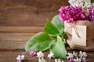 Branches of lilacs are in the basket of burlap on the background of wooden boards.