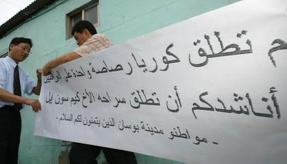 PUSAN RESIDENTS PREPARE A BANNER IN ARABIC FOR IRAQI MILITANTS.
