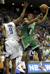 Boston Celtics guard Rajon Rondo shoots the ball as he is defended by Orlando Magic forward Rashard Lewis during their NBA basketball game in Orlando