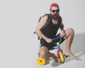 bearded serious man with bag, apple on bicycle toy
