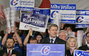 Supporters wave signs and cheer while Canadian Conservative Party leader Harper speaks during election rally in Toronto