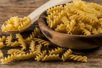 Pasta fusilli in a wooden bowl on wood background for healthy recipes.