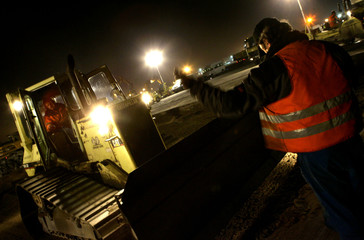 A worker directs a dozer at Frankfurt airport's 60-metre wide runway.