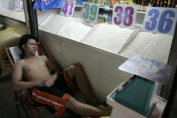A vendor takes a break beside rice for sale inside a market in Manila