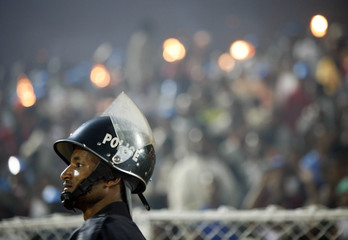 A policeman watches as people light fires during celebrations for the Ethiopian Millennium at a stadium in Addis Ababa