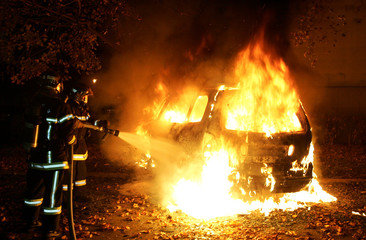 Firemen extinguish a burning car torched in Strasbourg's northern suburb of Cronenbourg