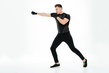 Portrait of a young healthy athlete man doing boxing exercises