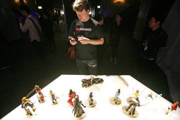 Yip of Los Angeles takes photographs of figurines from 'Final Fantasy' during 2006 E3 video game convention in Hollywood