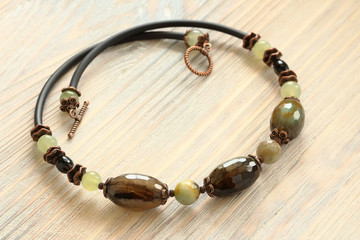Handmade necklace. Faceted agate, amazonite and jade on a light wooden background