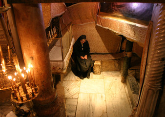 A nun sits praying at the grotto, where Christians believe Jesus was born, in Bethlehem's Nativity Church.