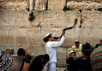 Jewish man blows horn during religious ceremony in front of Western Wall in Jerusalem's Old City