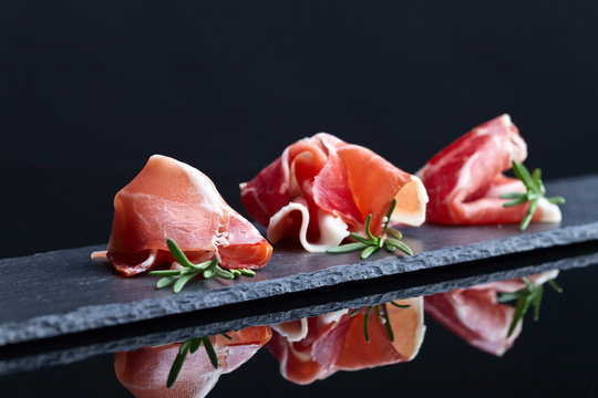 prosciutto with rosemary on a black background