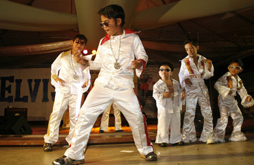 Children take part in an Elvis Presley look-alike and sing-alike contest held as a tribute to the 30th anniversary of Presley's death in Manila