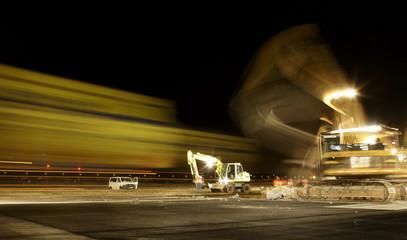 Workers use heavy equipment to remove a 15-metre long slice of Frankfurt airport's 60-metre wide runway.