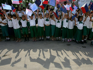 Filipino schoolchildren wave flags at the Tagbilaran airport in central Philippines