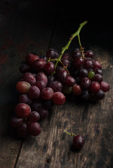 Organic grapes on a black plate on a dark vintage wooden rustic table. Dark and moody picture. Close up