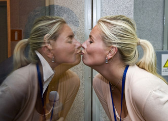 U.S. software pioneer Simonyi shares a kiss through the glass shield with his wife Lisa Persdotter at the Baikonur cosmodrome